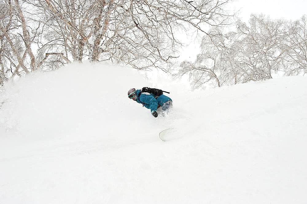 Snowboarder charging through the pow on a powder board