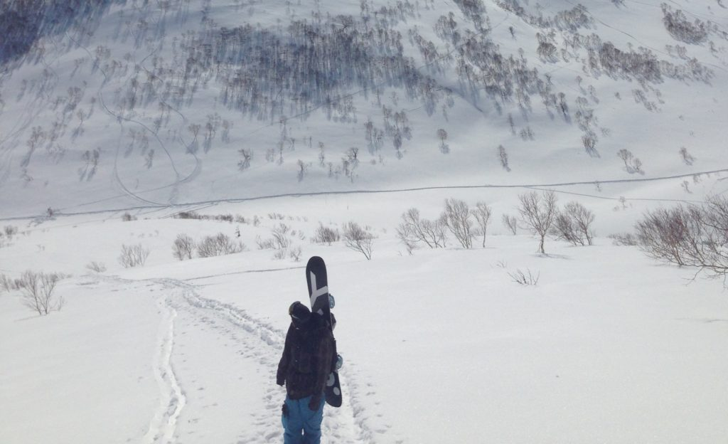 Snowboarder with powder board in the Niseko Backcountry