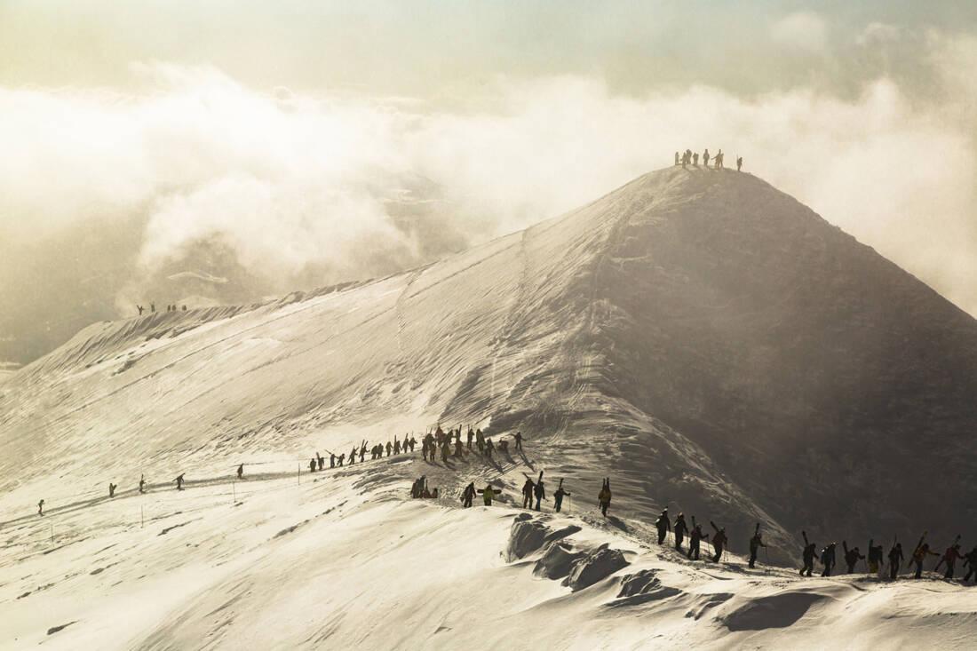 Skiers and snowboarders hike Annupuri mountain summit