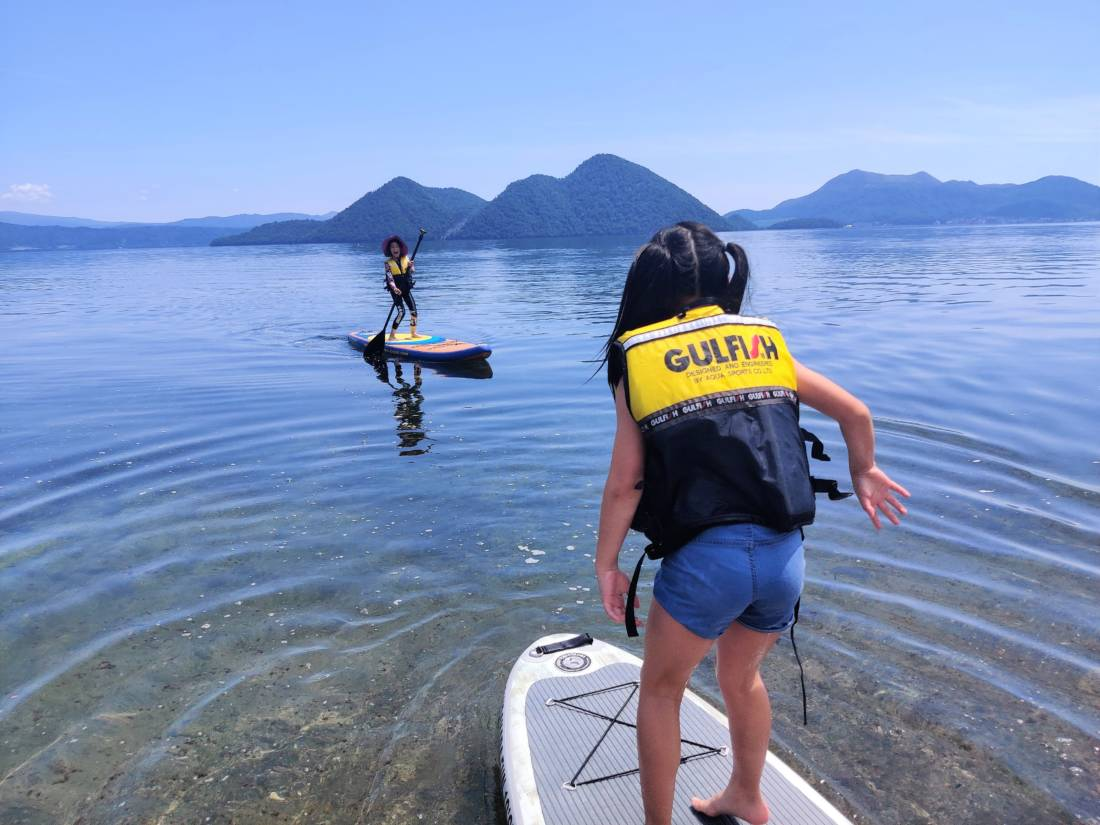 Children stand-up paddle boarding on the lake in summer in Niseko region
