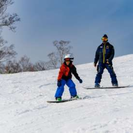 Instructor Adir during snowboard lesson with 7 year old